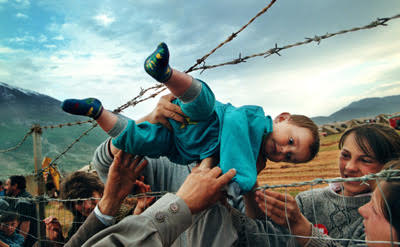 2000 Feature Photography Pulitzer Prize REUNIONMay 3, 1999 Kosovar refugee Agim Shala, 2 years old, is passed through the barbed wire fence into the hands of grandparents at the camp run by United Arab Emirates in Kukes, Albania. The members of the large Shala family were reunited here after fleeing Prizren in Kosovo during the conflict. . (The grandparents had just crossed the border at Morina). The relatives who just arrived had to stay outside the camp until shelter was available. The next day members of the family had tents inside. The fence was the scene of many reunions. When the peace agreement was signed, they returned to Prizren to find their homes only mildly damaged. There were tears of joy and sadness from the family as the children were passed through the fence, symbolic of the innocence and horror of the conflict.
